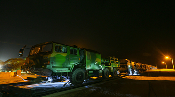 Soldiers unload military vehicles from rail car at night
