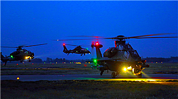 Helicopters lift off at night