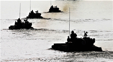Amphibious tanks launch smoke projectiles at sea