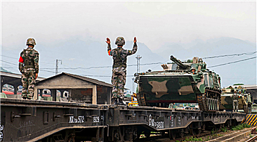 Soldiers secure armored vehicles onto flatbed railcar