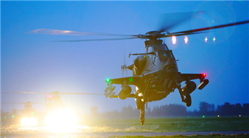 Army helicopters lift off at night