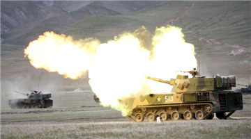 Self-propelled howitzer systems fire at targets in plateau area
