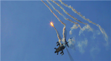 Attack helicopters deploy flares during training