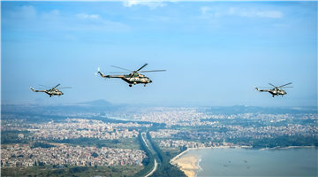 Transport helicopters fly over urban area