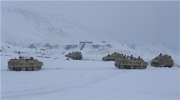 Armored vehicles rumble on snow-covered road